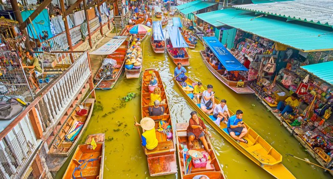 Chaotic boat traffic through the khlong (canal) of Ton Khem department of floating market with souvenirs and other goods in Damnoen Saduak. Фото efesenko-Deposit