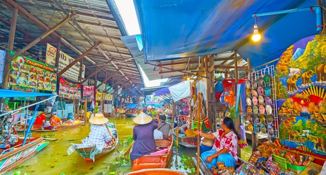 Make shopping in souvenir stalls of Ton Khem floating market in Damnoen Saduak. Фото efesenko - Depositphotos