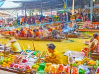 The sampan boat serves as the showcase and counter for the fruit vendor, offering variety of exotic fruits in Damnoen Saduak floating market. Фото efesenko-Deposit