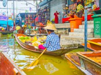 The old sampan of the fruit vendor with heaps of bananas, papayas, durians and mangoes in Ton Khem floating market in Damnoen Saduak. Фото efesenko-Deposit
