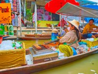 The food boat with grilled pork on skewers on khlong of Ton Khem floating market in Damnoen Saduak. Фото efesenko - Depositphotos