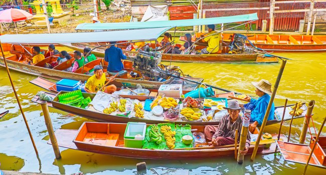 Damnoen Saduak floating market is nice place to buy fresh fruits and explore local trade traditions in Damnoen Saduak. Фото efesenko - Depositphotos
