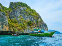The tourist ship and small longtail boat at the site of Viking Cave (Tham Phaya Nak), located under the tall cliff of Phi Phi Leh Island. Фото efesenko - Deposit