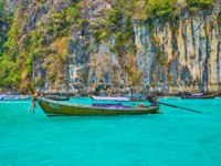 The old longtail boat bobs on the clear emerald waters of Pileh Bay lagoon on Phi Phi Leh Island. Фото efesenko - Depositphotos
