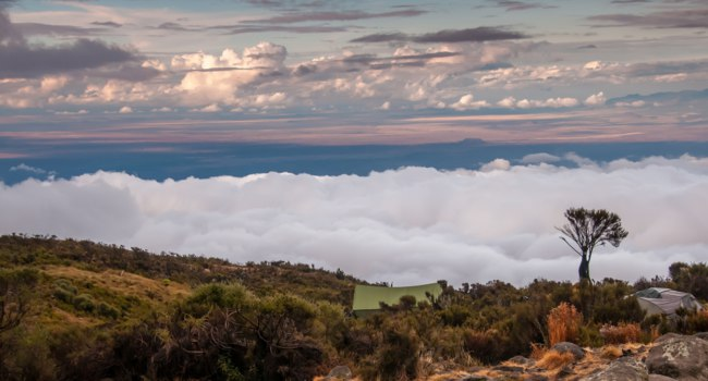 Kilimanjaro Camp site at Kikelelwa Cave at first light looking over the plains towards Kenya. Фото mountaintreks - Depositphotos