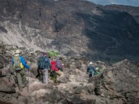Team descending to campsite with the Barranco wall and trail rising up from valley. Фото mountaintreks - Depositphotos