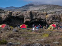 Танзания. Восхождение на гору Килиманджаро. Tents near some caves on the Shira Plateau, Kilimanjaro. Фото mountaintreks - Depositphotos