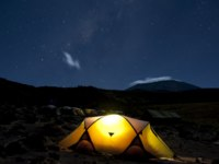 Kikelelwa Cave campsite on Rongai Route at night with Kilimanjaro shrouded in clouds under the stars and milky way. Фото mountaintreks - Depositphotos