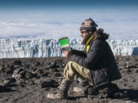 A trekker reading the Hemingway novel on the summit of Kilimanjaro with a glacier in background. Фото mountaintreks - Depositphotos