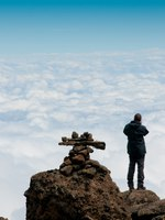 Looking out over the clouds and the African plains below on route to Kilimanjaro. Фото mountaintreks - Depositphotos