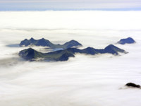 США. Аляска. Aerial View of an Aerial View of an Island Poking Through Ocean Fog in Kachemak Bay in Alaska. Фото wildnerdpix - Depositphotos