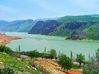 The green waters of the Achangaran reservoir with the Qurama Mountains on the background, Uzbekistan. Фото efesenko - Depositphotos