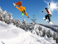 Сноубордисты. Snowboarders jumping against blue sky. Фото Tomas Marek Depositphotos