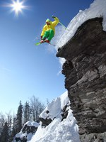 Горные лыжи. Skier jumping though the air from the cliff. Фото samot Depositphotos