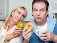 Couple in Kitchen with Fruit and Donuts. Фото Andy Dean - Depositphotos