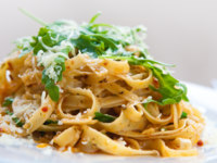 Delicious fettucine pasta with sundried tomato and rocket leaves. Фото Mayangsari - Depositphotos