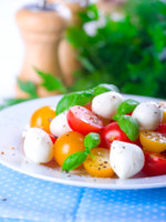 Caprese Salad with Mozzarella, Cherry Tomatoes and Basil. Фото Bienchen - Depositphotos