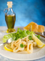 Fried squid rings with salad lemon and bottle of olive oil. Фото marcomayer - Depositphotos