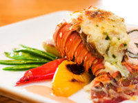 Lobster and stuffed chicken served with sweet peas, potatoes, peppers and oysters. Фото rohitseth - Depositphotos