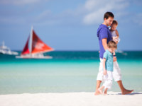 Мальдивы. Anantara Kihavah Villas. Father and two kids walking along the beach. Фото shalamov - Depositphotos