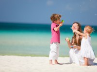 Мальдивы. Anantara Kihavah Villas. Mother and kids having fun on beach. Фото shalamov - Depositphotos