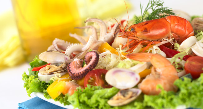Маврикий. Тарелка с морепродуктами. Seafood salad with shrimp, clams, octopus tentacles, calamari rings and prawns. Фото ildi_papp - Depositphotos