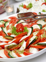 Delicious Italian caprese salad arranged on a party platter. Фото imagesetc - Depositphotos