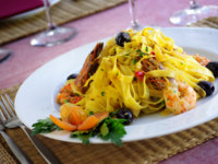 Italian dish of tagliatelle, shrimps and olives. Фото ccaetano - Depositphotos