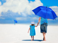 Father and daughter walking at beach. Фото shalamov - Depositphotos