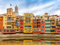 Испания. Каталония. Жирона. Colorful yellow, houses with the Catalan flag reflected in water river Onyar, in Girona, Catalonia. Фото olgacov -