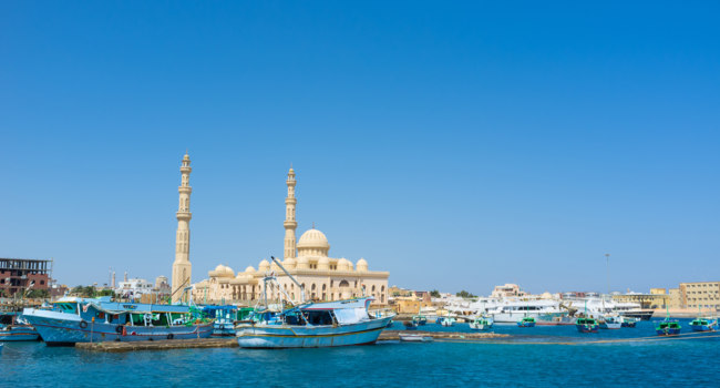 Египет. Хургада. The old fishing boats in port next to the fishing market and Central Mosque on the background, Hurghada, Egypt. Фото efesenko - Depositphotos