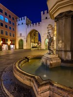 Германия. Мюнхен. Brunnenbuberl Fountain and Karlstor Gate in the Evening, Munich, Germany. Фото anshar - Depositphotos