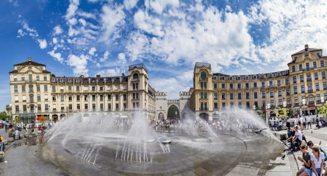 Германия. Бавария. Мюнхен. People walking along through the Karlstor gate in Munich and refresh at the fountain. Фото Hackman - Depositphotos