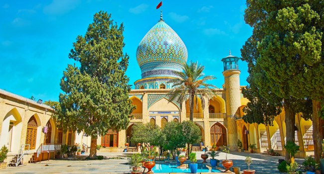 Exterior of medieval Ali Ibn Hamzeh Holy Shrine, decorated with arched niches, carved wooden Persian screens, scenic bulbous dome with pattern, Shiraz.Фотоefesenko-Dep