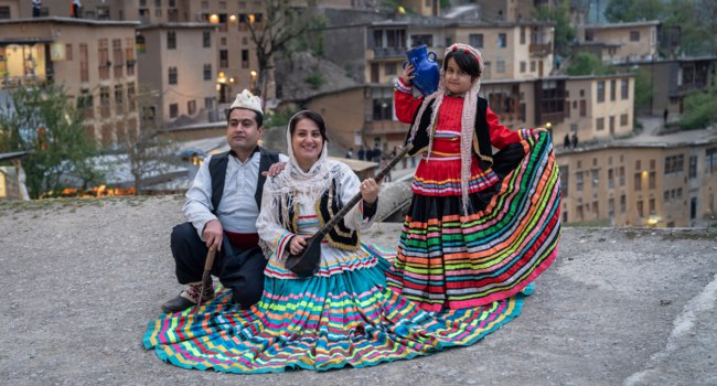 Иран. Деревня Масуле. Iranian family in Persian traditional clothes at village of Masuleh in Gilan province. Iran. Фото canyalcin - Depositphotos