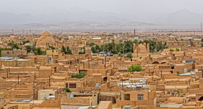 Иран. Йезд. Мейбод. Panoramic aerial view of the old desert city in Iran, sprawling mud-brick town that is at least 1800 years old. Фото dbajurin -Depositphotos