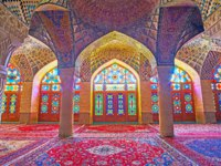 Interior of winter prayer hall of Nasir Ol-Molk mosque with beautiful stained glass windows, stone carved columns and fine tiled patterns in Shiraz. Фото efesenko-Deposit