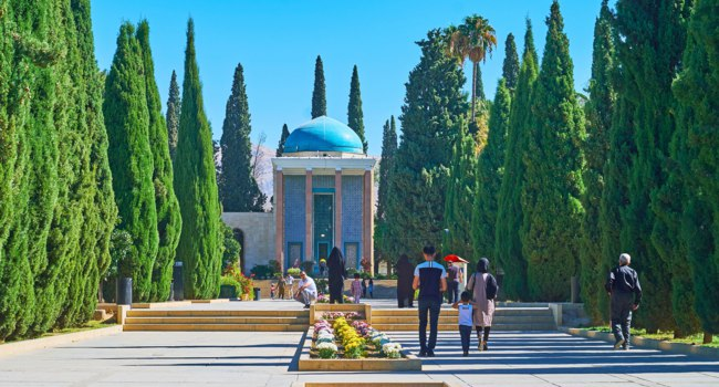 People walk the cypress alley of Tomb Saadi (Mausoleum of Sa'di, Sadiyeh) with flower bed amid the way and richly decorated pavilion Shiraz. Фото efesenko-Deposit