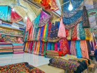 Interior of a stall in Vakil Bazaar with many colorful fabrics of silk, organza, cotton and other materials, decorated with embroidery, beads in Shiraz. Фото efesenko-Deposit