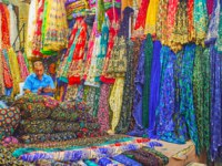 The merchant in textile stall of Vakil Bazaar among colorful fabrics, decorated with patterns, embroideries and lurex in Shiraz. Фото efesenko - Depositphotos