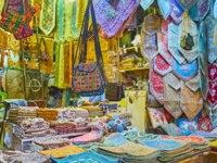 The souvenir stall with silk tapestries, dinner napkins, pillowcases, female bags, tablecloths and other goods, Vakil Bazaar, Shiraz, Iran. Фото efesenko - Depositphotos