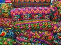 The heap of embroidered textiles, tapestries and bedcovers with colorful floral and authentic patterns in shop of Vakil Bazaar, Shiraz, Iran. Фото efesenko-Depositphotos