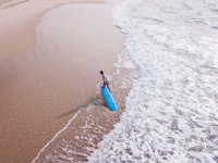Израиль. Ашдод. Aerial view of young woman in swimsuit pulling surfboard on sandy beach, Ashdod, Israel. Фото VeronikaGorBO - Depositphotos