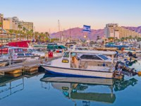 Израиль. Порт. The motor boats and yachts in Lagoona with the scenic rocky mountains of Jordan in the sunset lights in Eilat. Фото efesenko-Deposit