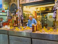 Израиль. Иерусалим. The senior merchant in stall of Mahane Yehuda market offers the dried fruits, sunflower seeds and various nuts in Jerusalem. Фото efesenko-Deposit