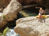 Tourist sunbathe in Ein Gedi spring. It's a very famous and popular oasis on the shore of Israel's Dead Sea, the lowest place on Earth.Фото lucidwaters-Depositphotos