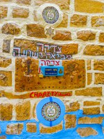 Израиль. Цфат. The donation box, built in the stone wall and surrounded by circle tiles and hebrew inscriptions in Safed. Фото efesenko-Depositphotos