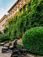Италия. Милан. A Milanese man dressed in a suit next to his vespa in front of a palace in Viale Luigi Majno covered in leaves, Lombardy, Italy. Фото Brasilnut-Deposit