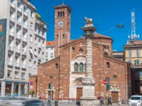Church of San Babila (Basilica di San Babila) timelapse and the column with lion on the top on Avenue Buenos Aires in Milan. Фото neiezhmakov-Deposit