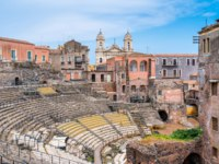 Италия. Сицилия. Катания. The roman theater in Catania, with the Church of St. Francis of Assisi on the background. Sicily. Italy. Фото e55evu - Depositphotos